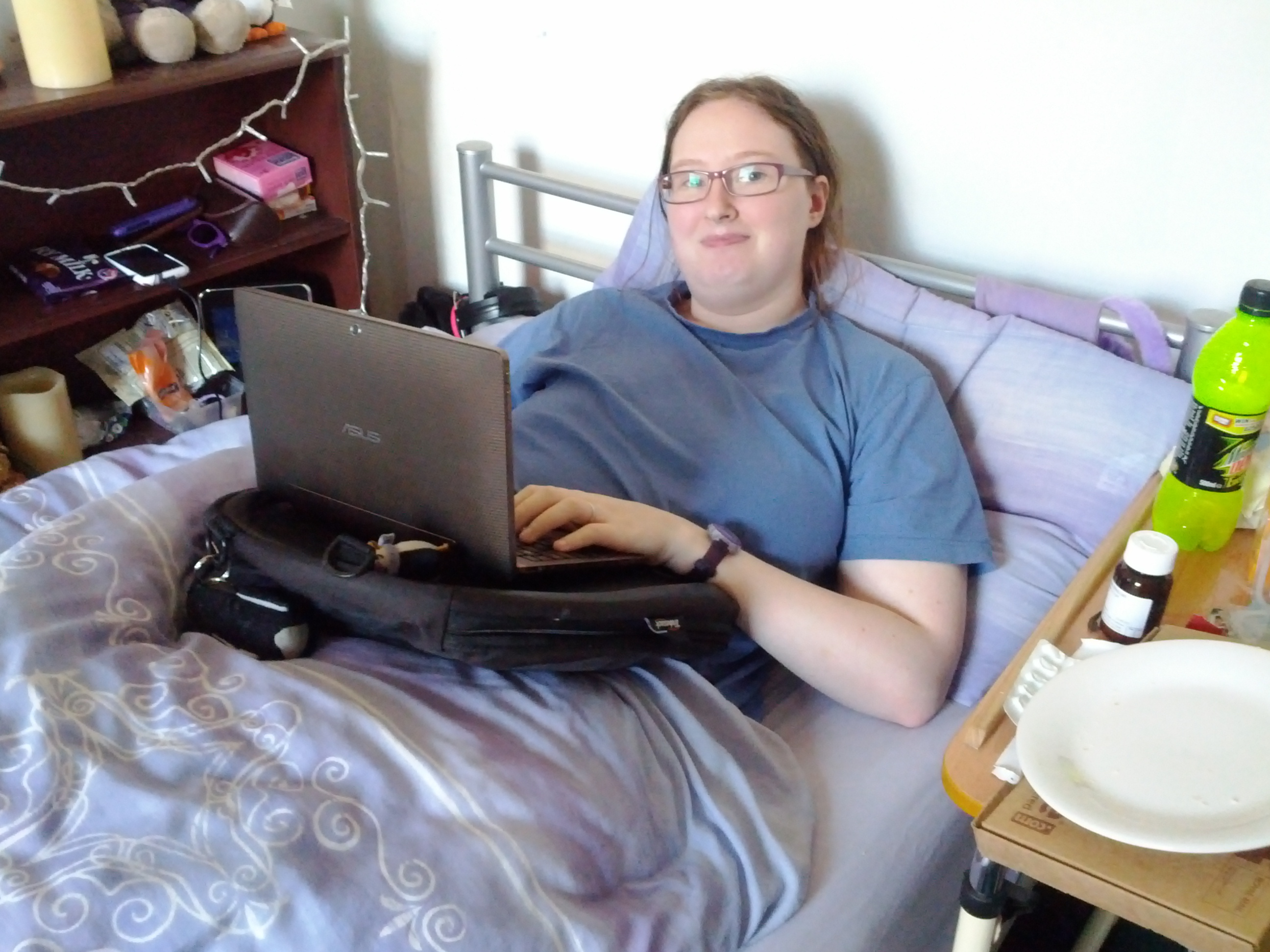 Danni in bed using a laptop on her trabasack