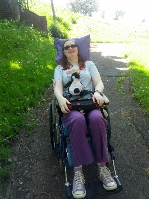 Danni outside in their wheelchair