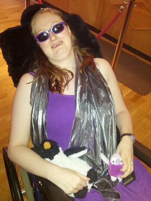 Danni at the prom. They are wearing a purple dress, a silver stole, sunglasses and a tiara. They are holding two penguins, a larger black and white one called Penguin, and a smaller sparkly purple one called Purple Penguin.