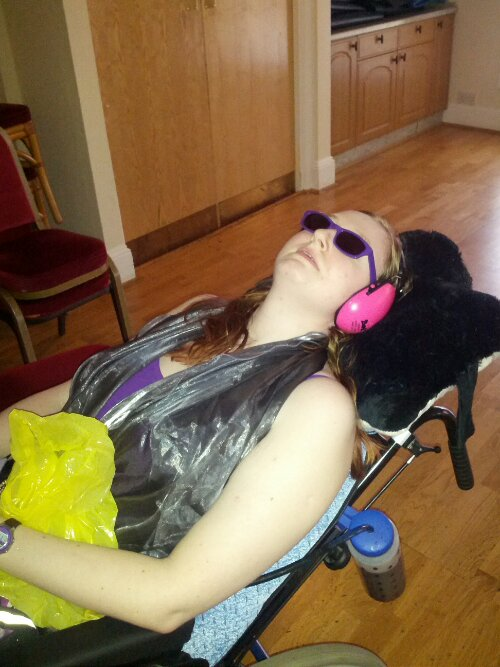 Danni lying in their wheelchair at the Prom. They are wearing sunglasses and pink ear defenders, and holding a sick bag.