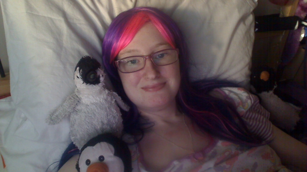 Danni wearing purple wig with pink at the front, surrounded by penguins.