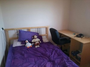 The same small bedroom, mostly filled with a double bed with purple bedding. There is a computer desk in the corner, with a computer chair in front of it. There is very little space between the two.