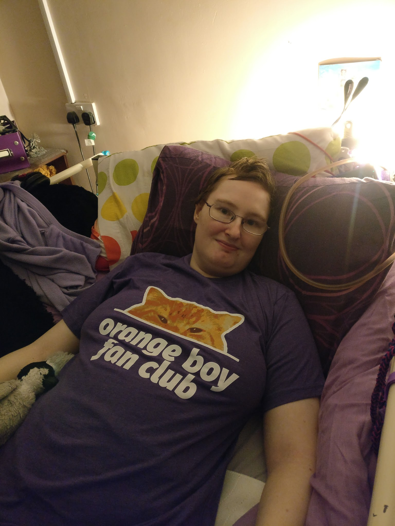 Danni is lying in bed, wearing a purple t-shirt with a picture of the top half of an orange cat's face (Bilbo), with orange boy fan club written underneath in white.