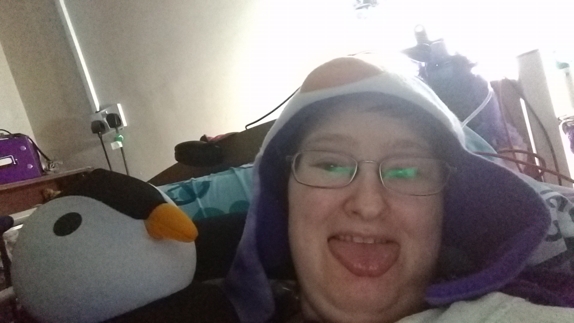 Danni is lying in bed wearing a purple penguin hat and sticking their tongue out.