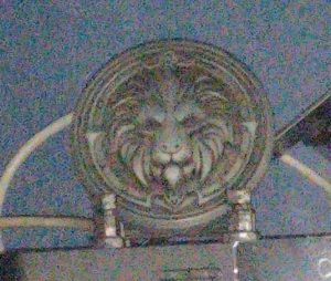 A metal ornament, which is round and has a lion's face and mane on it, representing the Alliance in World of Warcraft.