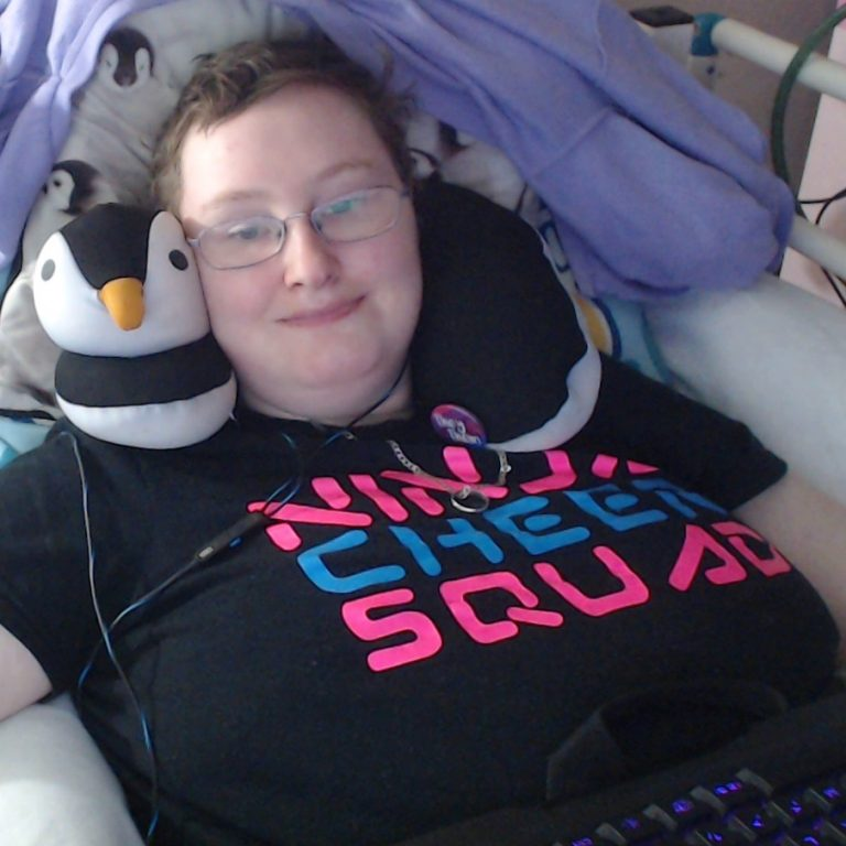 Danni is smiling at the camera. They are wearing a black t-shirt saying Ninja Cheer Squad. The Ninja and Squad are in bright pink, the Cheer is in bright blue. They are wearing a penguin neck cushion.