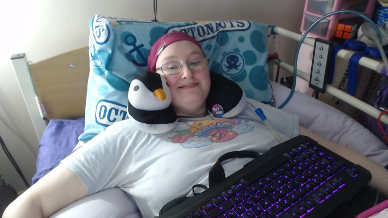 Danni is in bed wearing a blue t-shirt with Diablo 3 on the front with rainbows and unicorns, a penguin neck cushion, and a maroon scarf on their head. They have a computer keyboard resting on their tummy and is smiling.