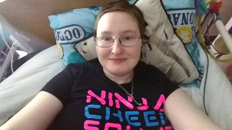 Danni is smiling in bed. They're wearing a black t-shirt with Ninja Cheer visible, in pink and blue.
