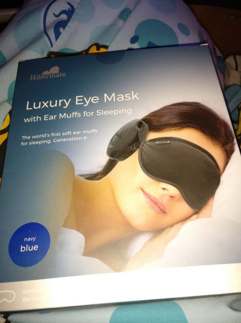 "A box with a picture of a woman wearing an eye mask with ear muffs, titled Hibermate, saying, ""Luxury Eye Mask with Ear Muffs for Sleeping"",   Below in smaller letters, ""The world's first soft ear muffs for sleeping. Generation 6""  There is a sticker saying navy blue."