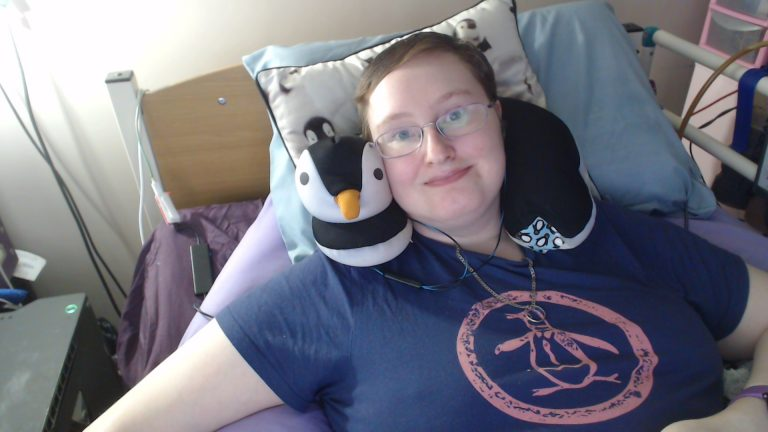 Danni is lying in bed, smiling at the camera. They are wearing a navy t-shirt with a coral penguin on the front and a penguin neck cushion.