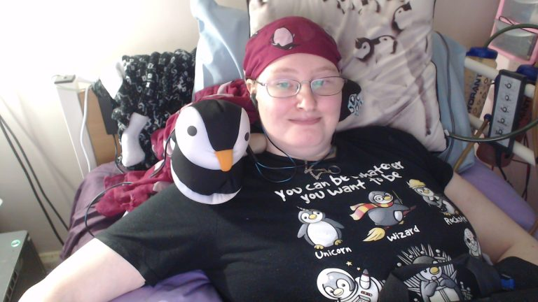 Happy Danni in bed, wearing a maroon headscarf with penguins on, and a black t-shirt with 6 penguins, showing various things you can be.