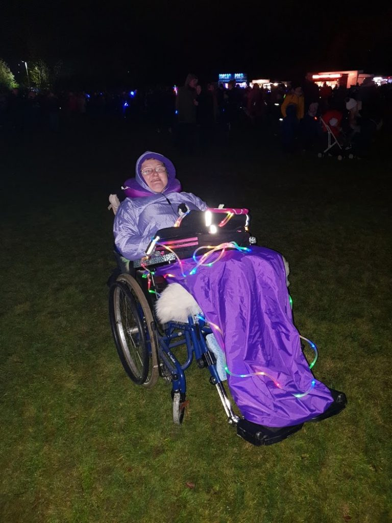 Danni at the local fireworks event. They are in their wheelchair, wearing purple waterproofs, with a tablet on their lap and a light rope around their body.