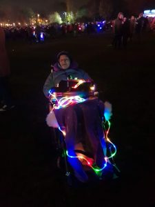 Another picture of Danni in their wheelchair in the park. This one is dark, other than a multicoloured rope light that is wound around their wheelchair.