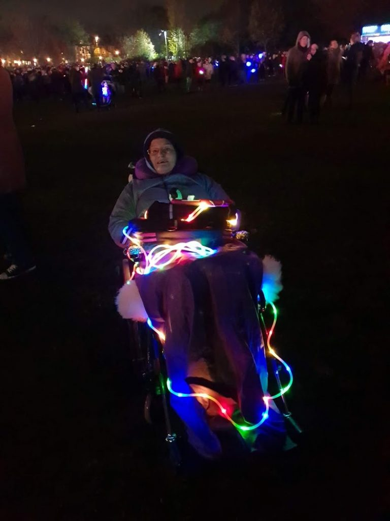 Danni lit up with rope lights on their wheelchair.
