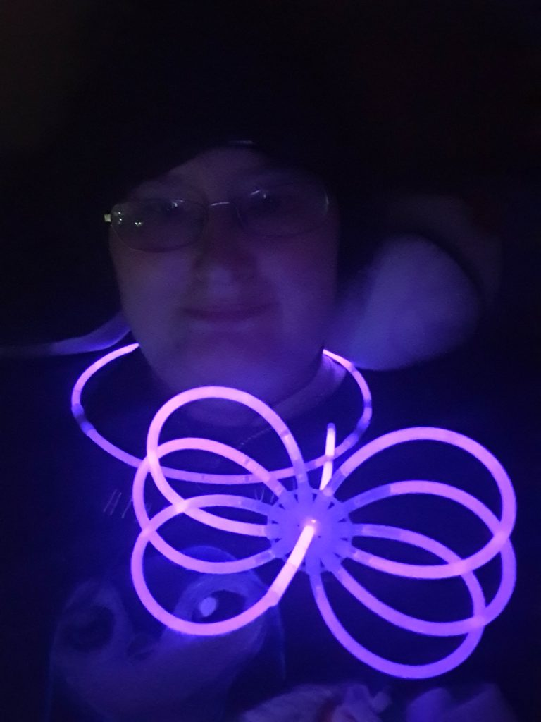 A very dark photo of Danni. Their face can just be seen by the light of a purple glow stick necklace and glow stick toy.