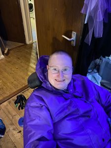Danni in their wheelchair. They are smiling and have a shaved head with only a tiny amount of hair left, and are wearing a purple coat and glasses.
