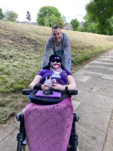 Danni and Martin outside. Danni is in their wheelchair, wearing a purple hat, purple sunglasses, a Pizza John mask (man's face in red and white with a moustache), a purple penguin top, pink bib and purple mermaid tail. They are holding Poseidon (a baby emperor penguin) and Purple Penguin.  Martin is standing behind, leaning on the wheelchair. He is a tall white man with short brown hair, a big smile, and is wearing a grey hoodie, white t-shirt with blue and green image, and blue jeans.